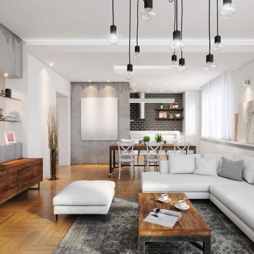 Ein helles Wohnzimmer mit Wohnküche mit einer großen, weißen Couch im Raum - und Tafelheizung
