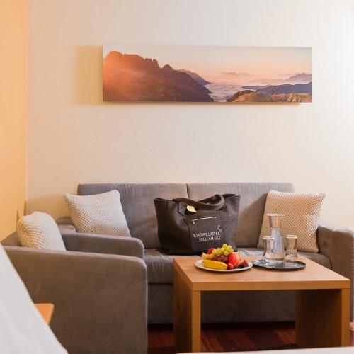Die Infrarotheizung in Bildmotiv Optik hängend über einer Couch neben einer Schiebetüre
