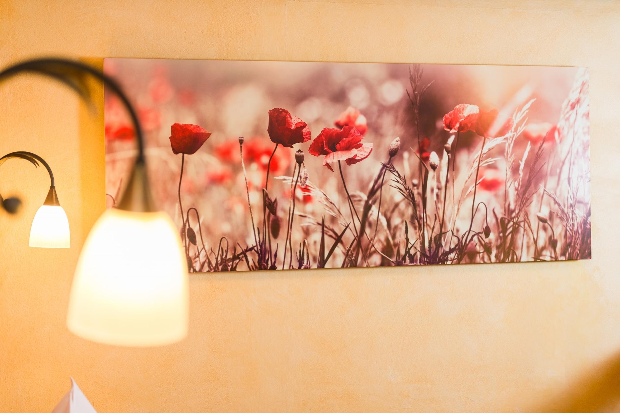 Die Infrarotbildheizung hängend an einer Wand neben einer Lampe