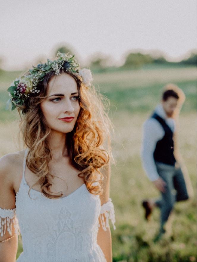 Ein Mädchen in einem weißen Kleid und einem Blumenkranz im Haar auf einer Wiese mit einem Mann im Hintergrund.