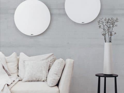 Zwei weiße Round-Infrarotheizungen in einem wohligen Zimmer.