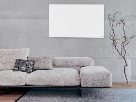 Die weiße WE-Line hängt an einem Betonhintergrund mit einer bequemen Couch davor.