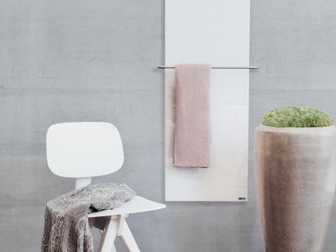 Handtuchtrockner mit rosa Badetuch auf einer Betonwand montiert mit einem weißen Sessel davor.
