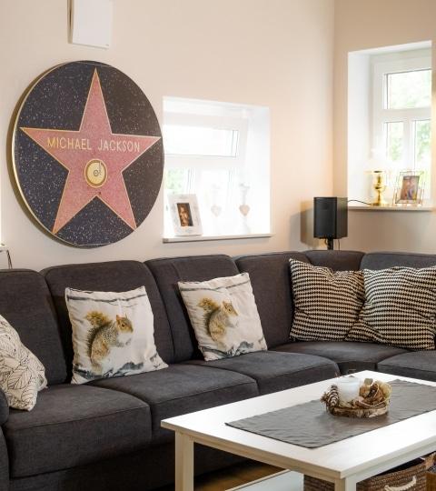 Die bedruckte Round beheizt ein schönes Wohnzimmer mit einer Couch im Vordergrund auf der Polster liegen.