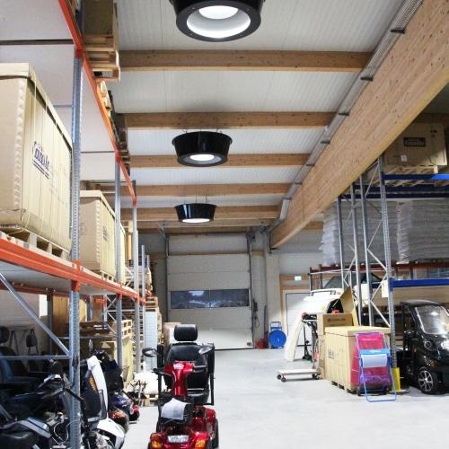 Die Infrarotdeckenheizung von Redwell hängt an der Decke einer Produktionshalle, in der kleine rote Penionistenfahrzeuge produziert werden.
