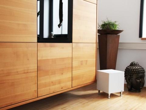 Infrarot Heizelement Cube in einem modernen Bürobereich vor einer Holz-Wohnwand.