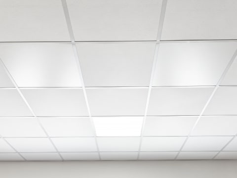 Eine Raster-Einlegedecke eines Büroraumes in weiß mit der Panelwave, als Deckenheizelement, die Infrarotwärme ausstrahlt.