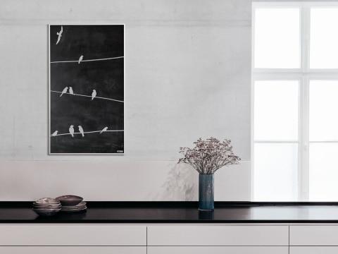 Tafleheizung an grauer Wand mit Blumen am Tisch darunter