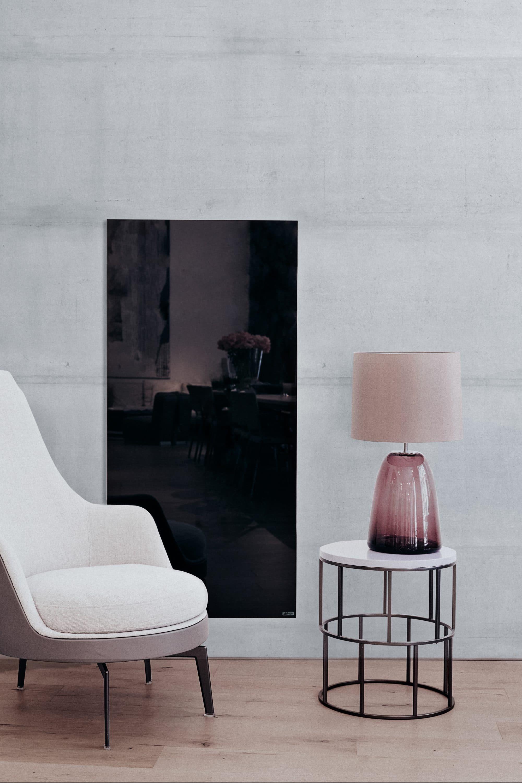 Moderne schwarze Redwell Infrarotheizung aus Glas auf Betonwand montiert mit Möbel davorstehend.