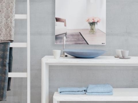 Ein Spiegel als Heizung strahlt angenehme Wärme in einem kühlen Badezimmer mit rustikaler Betonwand und einer Leiter als Handtuchhalterung aus.
