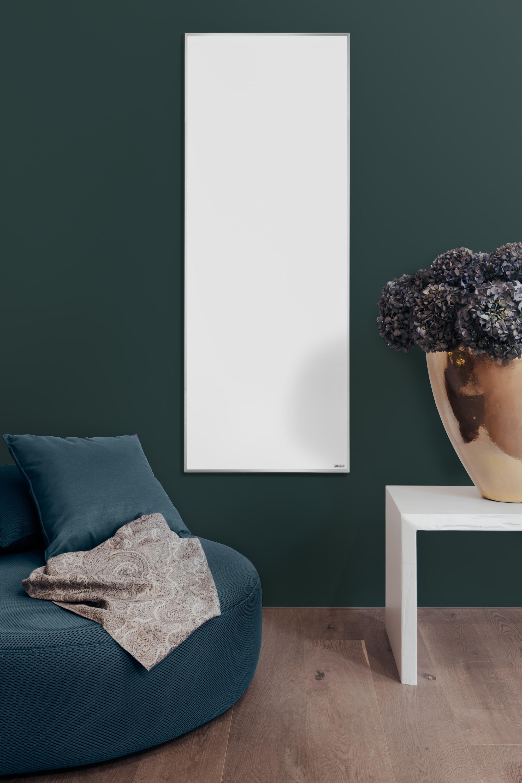 Die weiße Emailheizung strahlt angenehme Infrarotwärme in ein Wohnzimnmer mit grüner Wand.