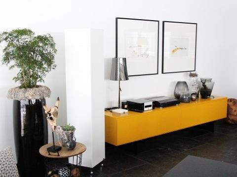 Infrarotheizung Tower in weiß in einem Wohnzimmer mit einem gelben Regal und Bilder an der Wand.