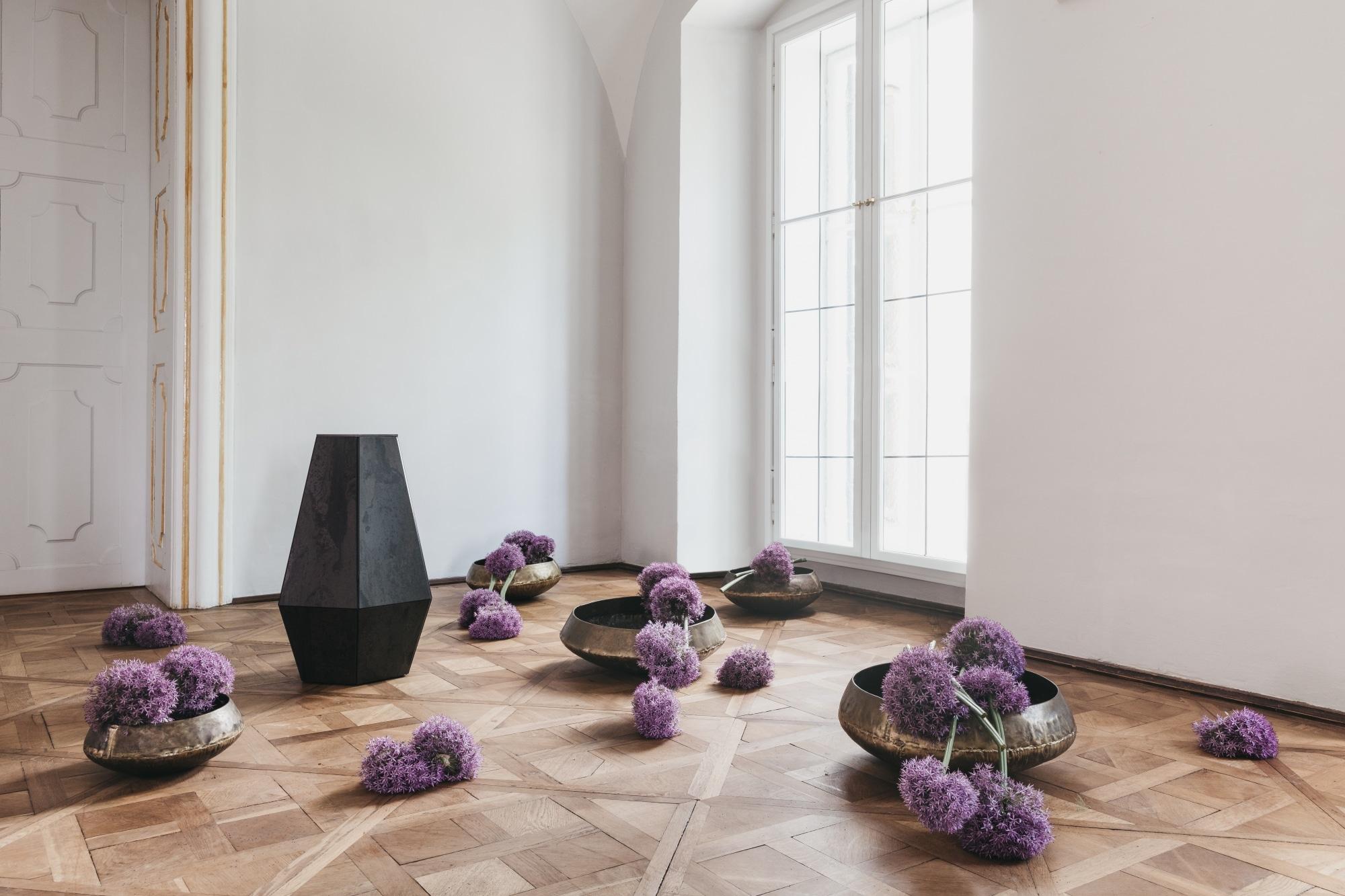 Der schwarze Diamant von Redwell steht umringt von Blumengestecken in einem Salon und zieht alle Blicke auf sich.