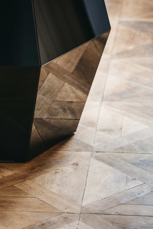 Detailfoto vom schwarzen Diamanten mit Spiegelung vom braunen Holzboden.