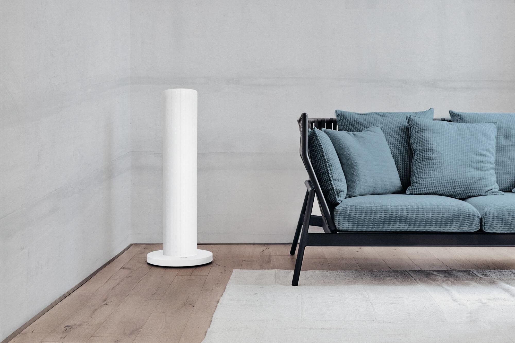 Die weiße Redwell Pipewave beheizt mit wohliger Wärme des Raum, in dem ein Sofa mit türkisen Kissen steht.