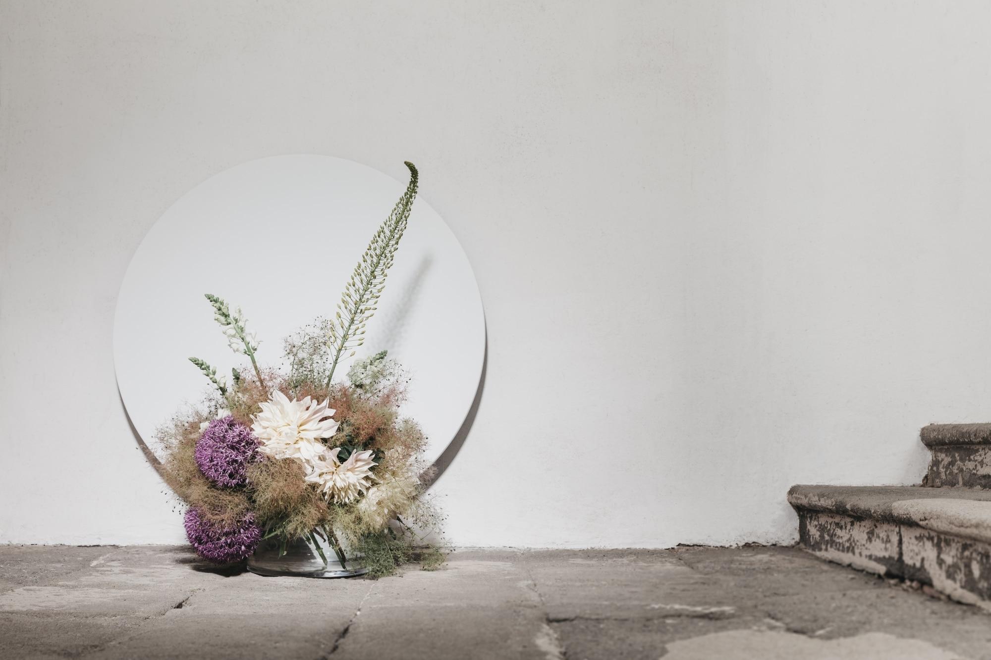 Die runde Infrarotheizung Round in weiß mit einem Blumengesteck davor lehnt an der Wand zu einem Stiegenaufgang.