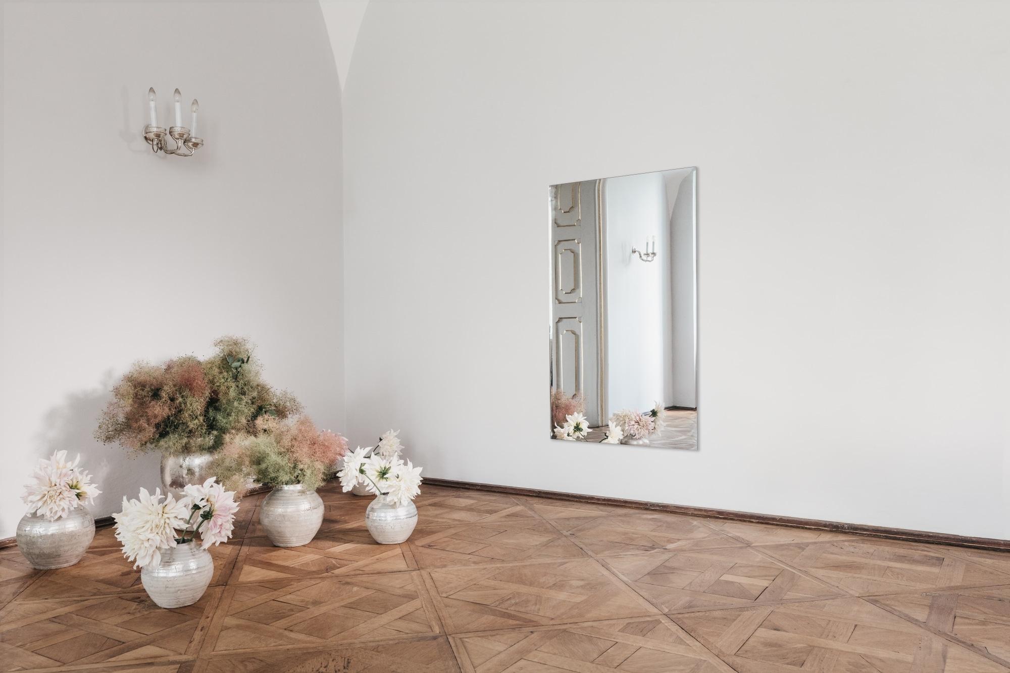 Die Redwell Spiegelheizung strahlt ihre Infrarotwärme in einem großen Salon eines Schlosses aus mit Blumendeko im Vordergrund.