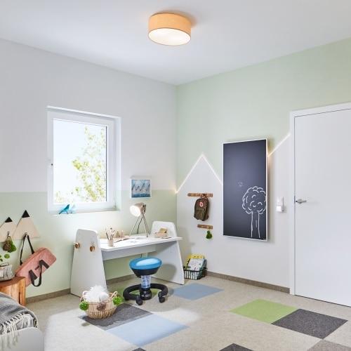 Ein freundliches Kinderzimmer in grün-weiss gehalten mit einer Redwell Tafelheizung auf der ein Baum gezeichnet wurde.